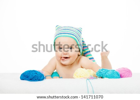Caucasian cute boy in funny colorful hat between balls of yarn - stock photo