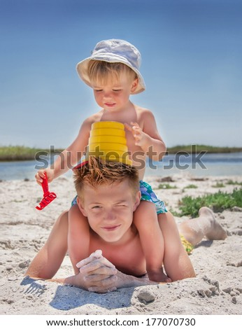 Caucasian cute boys (teenager and baby) are at the beach. Happy children are playing with toys in summer day. Summer vacation concept. Outdoor, close up.    - stock photo