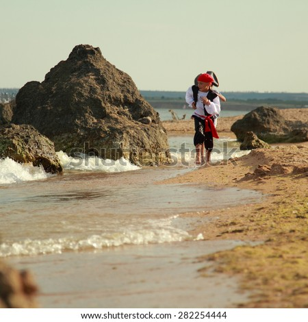 Caucasian cute kids play pirates on the sea/Girl and boy in pirate costumes running along the seashore - stock photo