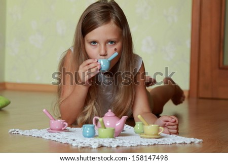 Caucasian cute little girl playing with children's set of dishes on the floor at home - stock photo