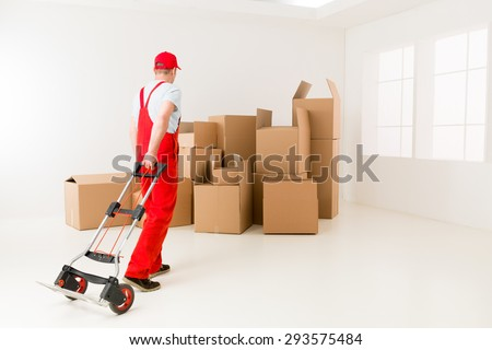 caucasian deliveryman in red uniform holding hand truck, getting ready to load cardboard boxes - stock photo