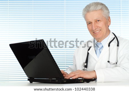 Caucasian doctor sits at a laptop - stock photo