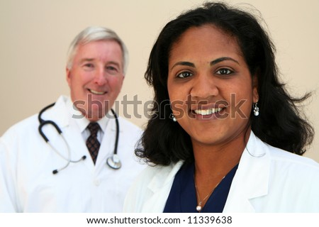Caucasian Doctor with minority Nurse - stock photo