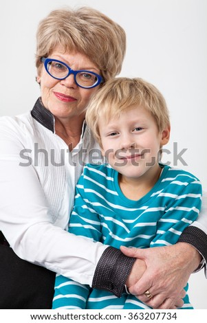 Caucasian elderly woman embracing young grandson, portrait on a gray background - stock photo