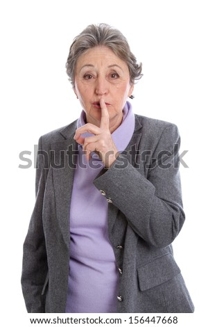 Caucasian elderly woman with finger on lips, isolated over white background.  - stock photo