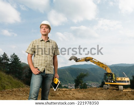 caucasian engineer standing on construction site holding digital tablet and measurement device
