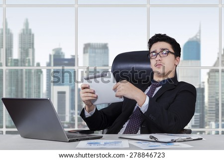 Caucasian entrepreneur sitting in the office while working with laptop and holding a digital tablet