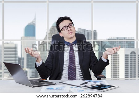 Caucasian entrepreneur sitting in the office with confused expression to find a solution