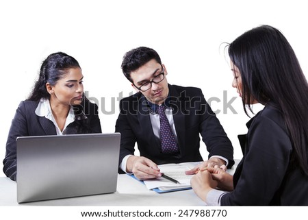 Caucasian entrepreneur with his assistant explaining a business document to his partner - stock photo