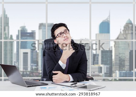 Caucasian entrepreneur working on desk with laptop while thinking idea and looking up