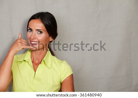 Caucasian ethnicity woman gesturing a phone call and looking at camera in green blouse and hair back on grey texture background - stock photo