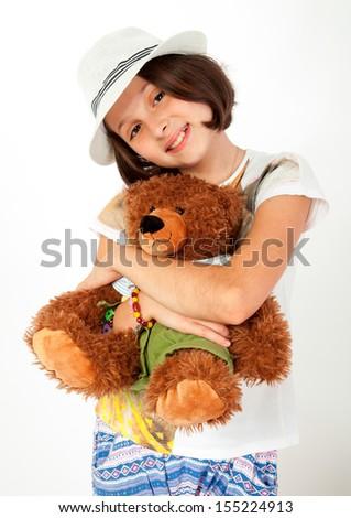 Caucasian, european girl with brown hair and blue eyes, hugging her teddy bear, stuffed animal