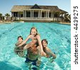 Caucasian family at pool with clubhouse in background. - stock photo