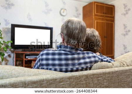 Caucasian family from three people sitting on the couch and watching tv, rear view, isolated white screen - stock photo