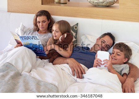 caucasian family laying in bed, mother and daughter reading father and son playing games on tablet device - stock photo