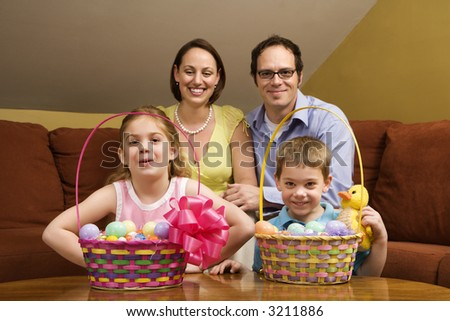 Caucasian family with Easter baskets looking at viewer.