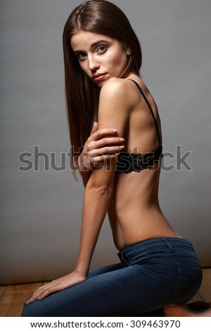 Caucasian fashion model wearing bra and jeans posing sitting on the floor