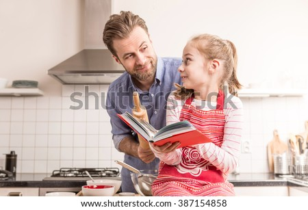 Caucasian father and daughter having fun while getting ready to bake cookies in the kitchen - happy family time. - stock photo