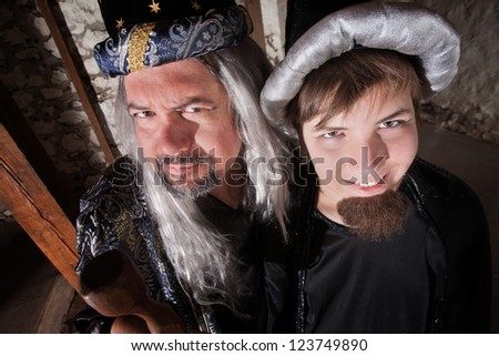 Caucasian father and son wizards standing next to each other - stock photo