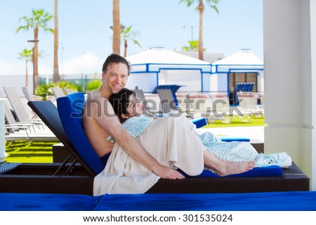 Caucasian father holding disabled son on blue poolside lounger, drying off after swimming. Child has cerebral palsy.  - stock photo