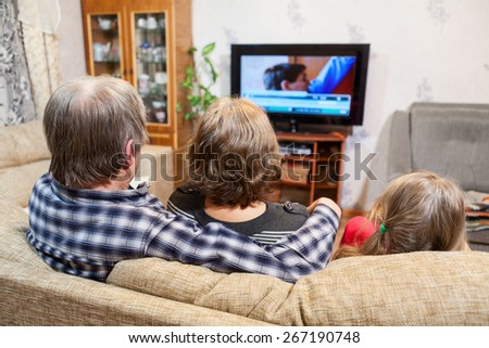 Caucasian father, mother and daughter sitting on the couch and watching tv set - stock photo