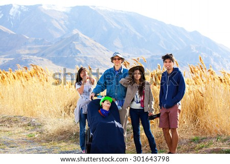 Caucasian father standing by field of tall grasses with biracial children. Youngest child in wheelchair has cerebral palsy. - stock photo