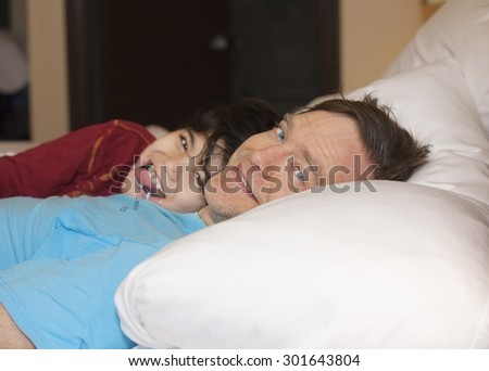 Caucasian father taking a nap with young disabled biracial son, in bed, laughing and talking together. Child has cerebral palsy.  - stock photo