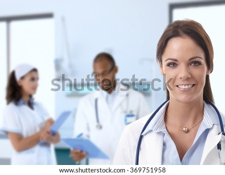 Caucasian female doctor at hospital looking at camera, smiling, medical staff working in background. - stock photo