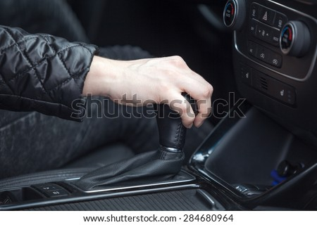 Caucasian female hand changing levels of automatic car gearbox, driver seat close up view - stock photo