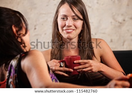 Caucasian female holding coffee cup and talking with friend - stock photo