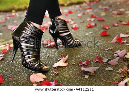 Caucasian female model posing fashion design shoes. Shallow depth of field, focus at forward shoe.