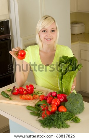 Caucasian female presenting tomatoes and lettuce holding in hands by kitchen counter top
