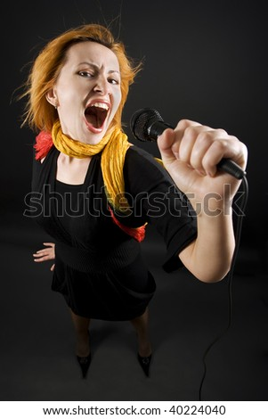 Caucasian female singing into microphone. Shot on wide angle.