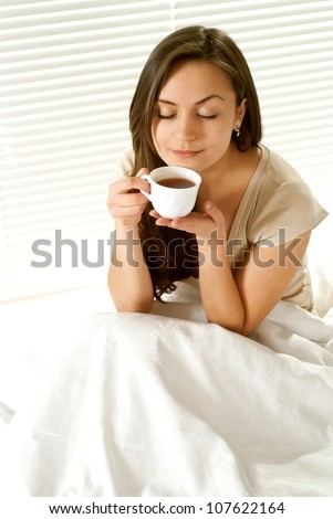 Caucasian female sitting on a bed with a cup on a light background - stock photo