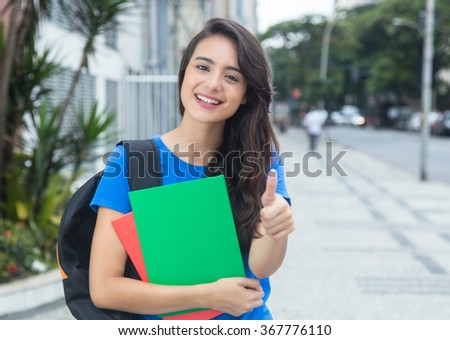 Caucasian female student with blue shirt showing thumb in the city - stock photo