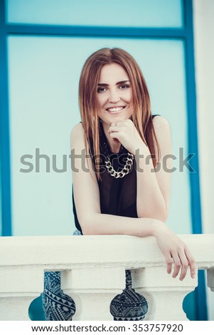 Caucasian girl city portrait. Woman smiling outside in evening light on street.  Young cheerful fashion woman
