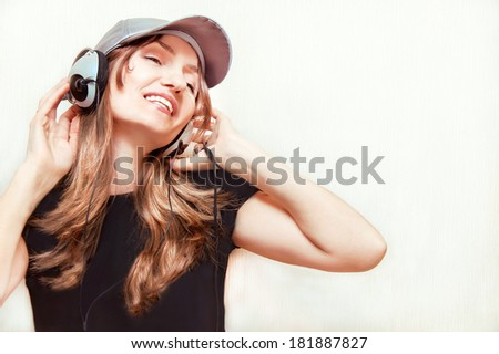 Caucasian girl is listening music with headphones. Young woman is enjoying of music. Happy relaxing beautiful female model.  Indoor. Copy space.