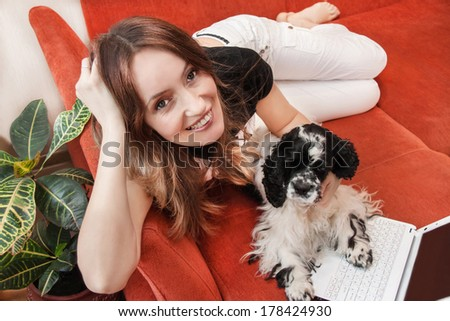 Caucasian girl is resting with dog and laptop on the sofa. Indoor. - stock photo