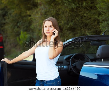 Caucasian girl on a cell phone service or tow truck traffic near the cabriolet car - stock photo