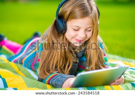 Caucasian Girl Playing Tablet Wearing Wireless Headphones. Ten Years Old Girl Listen Music and Playing Games on the Tablet Device. - stock photo