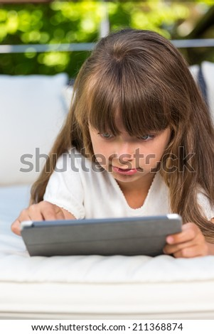 Caucasian girl playing with her tablet outdoors on the patio during summer time.