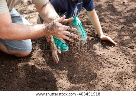 Caucasian girl shaking soil dirt with her hands - stock photo