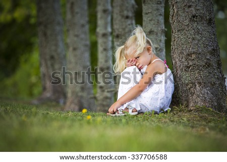 caucasian girl sitting in the grass being shy