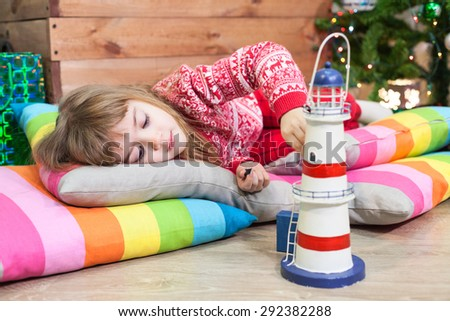 Caucasian girl sleeping on the home floor in Christmas clothes at the night before - stock photo