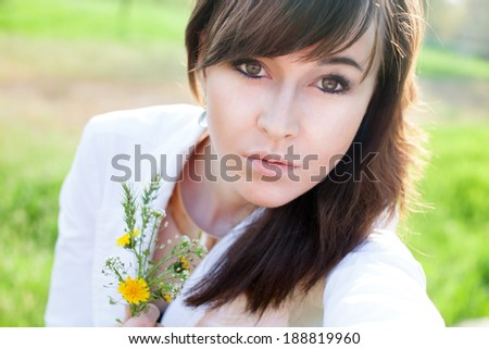 Caucasian girl taking selfie by her phone. Holding bouquet - stock photo