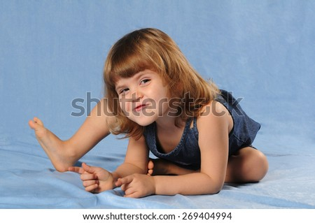 Caucasian girl two years old sitting almost lying on blue textile background in studio, smiles, frolics and looking at camera. - stock photo