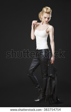 Caucasian girl wearing tight leather pants and white top and high heels standing and holding jacket in her hand. - stock photo