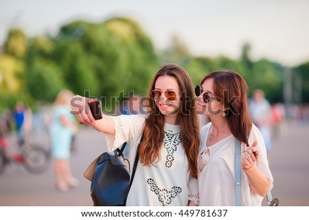Caucasian girls making selfie outdoors. Young tourist friends traveling on holidays smiling happy.