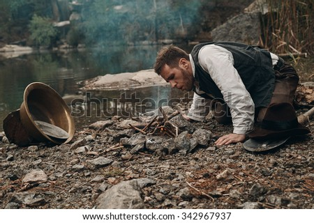 caucasian gold digger in retro clothes making fire after hard work. He wears shirt, leather pants and boots.  Sky is cloudy and grey. There is gold mining equipment in the frame.