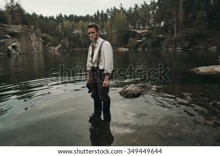caucasian gold digger in retro clothes smokes cigarette while standing in lake with rocky bank after hard work. He wears shirt, leather pants, galluses and boots.  Sky is cloudy and grey.